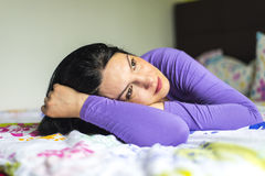 Sad woman thinking in bed royalty free stock photography