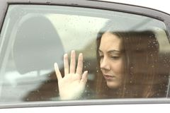 Sad woman inside a car during a roadtrip. Sad woman touching window ine a car during a roadtrip a rainy day royalty free stock image