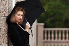 Sad woman with umbrella in the rain Stock Photos