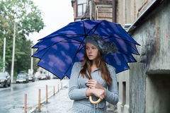 Sad woman under an umbrella. Sad beautiful young woman in a knitted hat standing under an umbrella in the rain on a city street Royalty Free Stock Photography