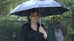 Sad Woman under umbrella. At heavy rain at the funeral