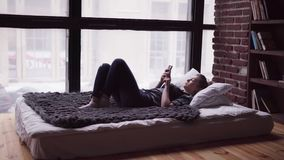 Sad woman using smartphone, lying on bed by window, overlooking city street stock video