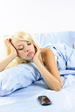 Sad woman waiting by phone in bed Stock Photo