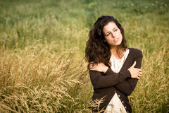 Sad woman walking in nature. Sad shivery woman in brown sweater jacket hugging herself and walking in nature field on late summer cold day. Sadness, melancholia Stock Photo