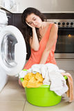 Sad woman washing clothes in machine Royalty Free Stock Photo