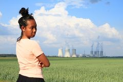 Sad woman watching Nuclear power plant Dukovany. Sad Papuan woman with black hair and yellow t-shirt watching Nuclear power plant Dukovany with cooling towers royalty free stock photos