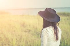 Sad woman wearing black hat standing in a meadow. Background Stock Photography