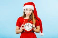 Sad woman wearing Santa costume holding clock Royalty Free Stock Images