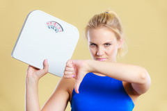 Sad woman with weight gain thumb down sign. Frustrated sad blonde girl holding scales, making thumb down gesture sign. Weight gain, time for slimming weightloss Royalty Free Stock Photo
