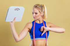 Sad woman with weight gain thumb down sign. Frustrated sad blonde girl holding scales, making thumb down gesture sign. Weight gain, time for slimming weightloss Stock Photography