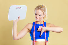 Sad woman with weight gain thumb down sign. Frustrated sad blonde girl holding scales, making thumb down gesture sign. Weight gain, time for slimming weightloss Stock Photos