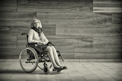 Sad woman on wheelchair. Sad woman sitting on wheelchair in the hospital, looking straight to the camera stock images