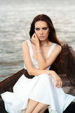 Sad Woman in White Dress Sitting in an Old Boat Stock Photography