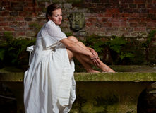 Sad woman in white dress sitting on a stone bench. Woman in a white classical dress sitting on an old stone bench outdoor in a romantic park. She has a sad stock images