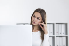 Sad woman in white office looking at screen Royalty Free Stock Image