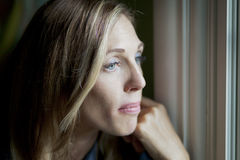 Sad woman at the window royalty free stock image