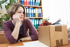 Sad woman in workplace after dismissal Stock Photos