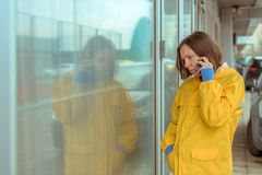 Sad woman in yellow raincoat talking on mobile phone. Out on the street while it`s raining stock images