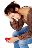 Sad women holding heart in her hand. Stock Photography