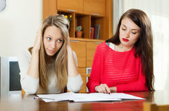 Sad women looking financial documents Royalty Free Stock Photo