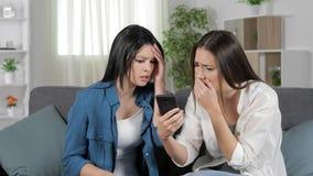 Sad women reading bad news on smart phone stock video footage