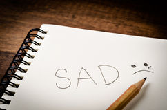 SAD word on diary book with wooden pencil. Royalty Free Stock Images