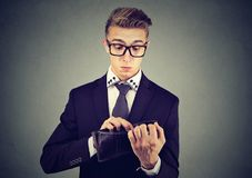 Sad worried young business man looking into his wallet with no money royalty free stock photography