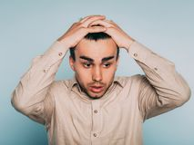 Sad worried scared afraid man pull hair out emotion. Sad worried distraught scared afraid man pulling hair out. portrait of a young brunet guy on light stock photos