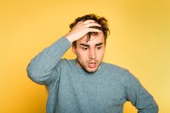 Sad worried scared afraid man pull hair out emotion. Sad worried distraught scared afraid man pulling hair out. portrait of a young handsome brunet guy on yellow stock photo