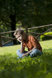 Sad/worried little boy. Sitting outdoors Stock Photos