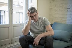 Sad and worried man with grey hair sitting at home couch looking. 40s or 50s sad and worried man with grey hair sitting at home couch looking depressed and royalty free stock photo