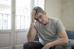 Sad and worried man with grey hair sitting at home couch looking. 40s or 50s sad and worried man with grey hair sitting at home couch looking depressed and Royalty Free Stock Photos