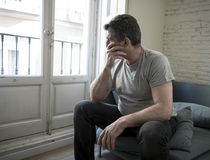 Sad and worried man with grey hair sitting at home couch looking. 40s or 50s sad and worried man with grey hair sitting at home couch looking depressed and Stock Photo