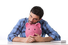 Sad worried man in stress with empty piggy bank. Attractive young lad feeling sad, leaning on empty pink piggy bank in bad financial situation concept wearing Royalty Free Stock Images