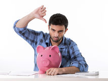 Sad worried man in stress with piggy bank in bad f. Attractive broke man worried in stress feeling sad,  with empty pink piggy bank in bad and kaput  financial Stock Image