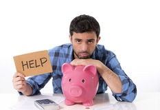 Sad worried man in stress with piggy bank in bad f. Young attractive broke man in stress feeling sad, leaning on empty piggy bank with calculator accounting his Stock Photos