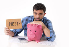 Sad worried man in stress with piggy bank in bad financial situation. Young attractive broke man worried in stress, feeling sad and desperate on empty pink piggy Stock Photo