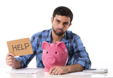 Sad worried man in stress with piggy bank in bad financial situation. Young attractive broke man worried in stress, feeling sad and desperate on empty pink piggy Royalty Free Stock Photos