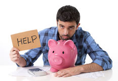 Sad worried man in stress with piggy bank in bad financial situation. Young attractive broke man worried in stress, feeling sad and desperate on empty pink piggy Stock Photos