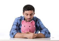 Sad worried man in stress with piggy bank in bad financial situation. Young attractive broke man worried in stress, feeling sad hugging empty pink piggy bank in Royalty Free Stock Photography
