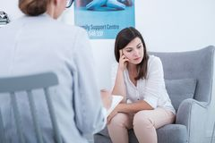 Sad and worried mother talking to a psychologist about her child royalty free stock photography