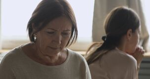Sad worried older mother feel hurt after fight with daughter