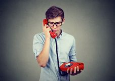 Sad worried teenager man talking on an old fashioned telephone stock photo