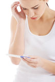 Sad, worried woman holding pregnancy test. Stock Image
