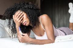 Sad and worried woman with a pregnancy test on bed. Woman on bed sad and worried with a pregnancy test Royalty Free Stock Photos