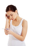 Sad, worried woman with pregnancy test. Isolated on white stock photography