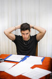 Sad or worried young man working or studying at. Home sitting at table with paper sheets in front of him Stock Photo