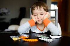 Sad 4 year old boy sitting at the table with pills Stock Photo