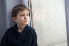 Sad 7 years boy child looking out the window. Royalty Free Stock Photos