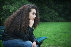 Sad young woman sitting on bench stock photos